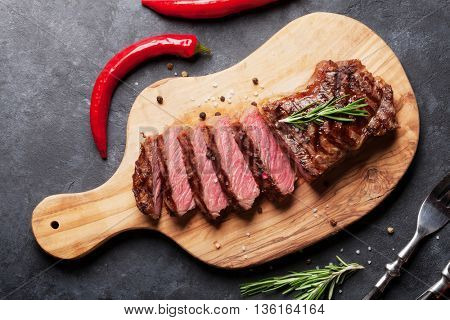 Grilled sliced beef steak on cutting board over stone table. Top view