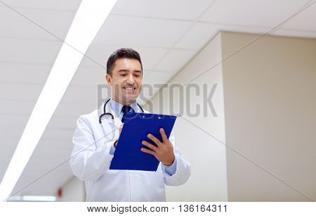 clinic, people, health care and medicine concept - smiling doctor with clipboard at hospital corridor