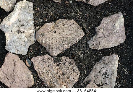 Natural Texture: Stones Lie On A Black Soil