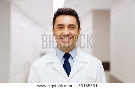 healthcare, profession, people and medicine concept - smiling male doctor in white coat at hospital