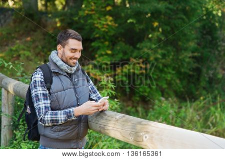 travel, tourism, hike, technology and people concept - happy man with backpack and smartphone texting message outdoors