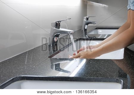 White Washbasin And Faucet On Granite Counter With Hand Washing