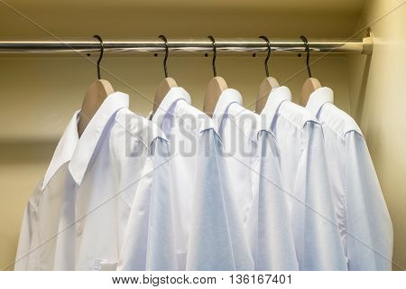 Close Up Of White Shirts Hanging On Coat Hanger In Wardrobe