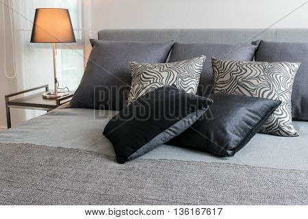 Sylish Bedroom Interior Design With Black Patterned Pillows On Bed And Decorative Table Lamp.