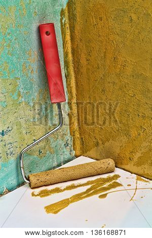 Roller paintbrush near grunge yellow painted wall.Toned image.