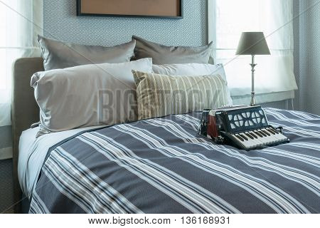 Stylish Bedroom Interior Design With Striped Pillows And Decorative Accordion On Bed