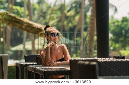 Sexy woman in bikini at beach cafe bar. Girl enjoying a cup of coffee outside. Smiling happy Caucasian woman near ocean beach. young beautiful woman relaxing on tropical vacation