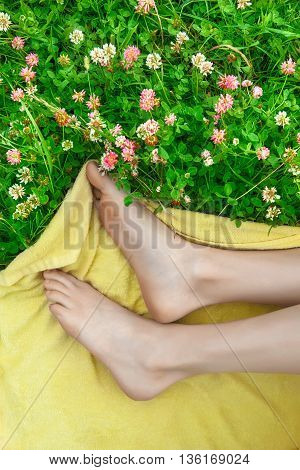 feet of young girl lying on field colors