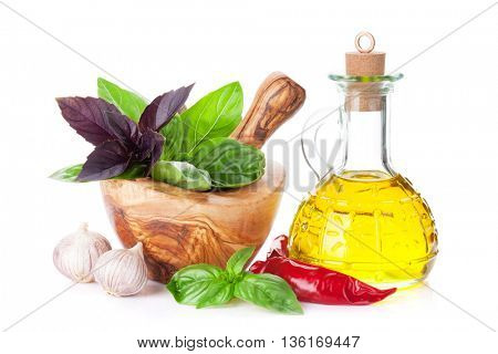 Fresh garden herbs in mortar, olive oil. Basil, rosemary, dill. Cooking ingredients. Isolated on white background