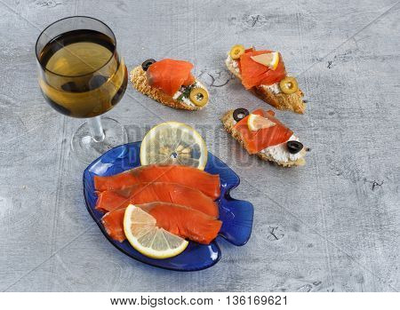 Tasty various italian sandwiches with seafood against rustic wooden background. Crostini with cheese red fish and olives glass of wine horizontal top view