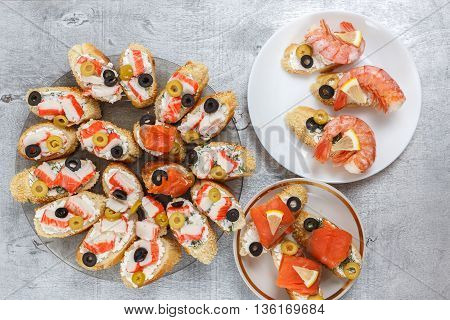 Tasty various sandwiches with seafood against rustic wooden background. Crostini with cheese shrimps mussels red fish crab sticks lemon olives on plates horizontal top view