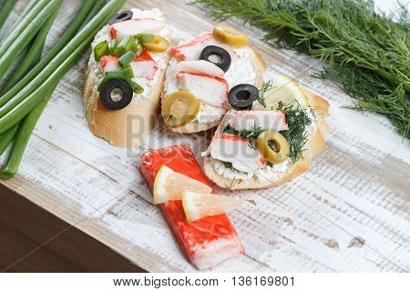 Tasty various italian sandwiches with seafood against rustic wooden background. Crostini with cheese crab sticks olives and herbs horizontal view with selective focus