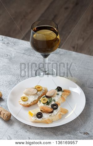 Tasty various italian sandwiches with seafood against rustic wooden background. Crostini with cheese mussels and olives on white plate and wine close up with selective focus