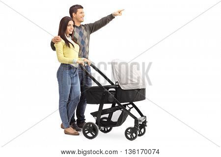 Young parents pushing a baby stroller and the man showing something to his wife isolated on white background
