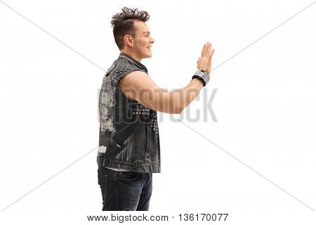 Cheerful punk rocker waving to someone with his hand isolated on white background