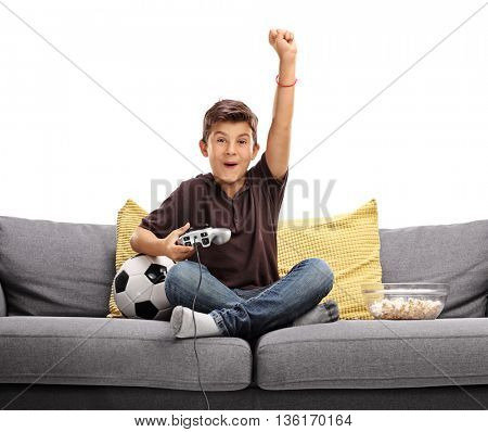 Joyful kid playing soccer video game and celebrating a goal seated on a sofa isolated on white background