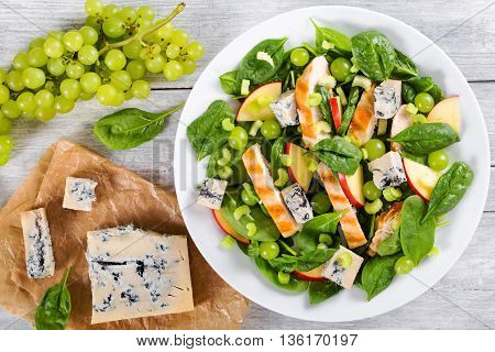 grilled chicken breast grapes spinach gorgonzola cheese and apple salad on a white dish on a table mat on white wooden background view from above