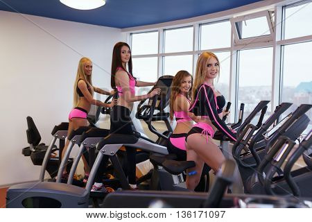 Image of sexy girls training on simulators in fitness centre
