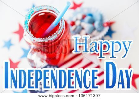 anniversary, celebration, patriotism and holidays concept - close up of juice glass, american flag and candies at 4th july party with happy independence day words