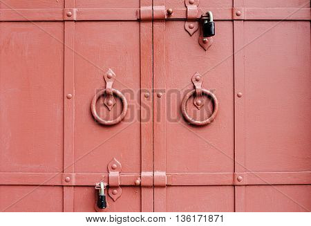 Old red gate doors with locks closeup shot