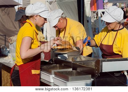 KYIV, UKRAINE - JUN 4, 2016: Fast-food kitchen workers cooking dishes in friture for hungry customers of outdoor fair on June 4, 2016. Kiev is the 8th most populous city in Europe.
