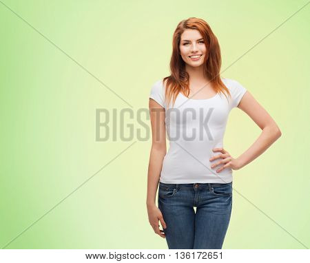 emotions, expressions, advertisement and people concept - happy smiling young woman or teenage girl in white t-shirt over green natural background