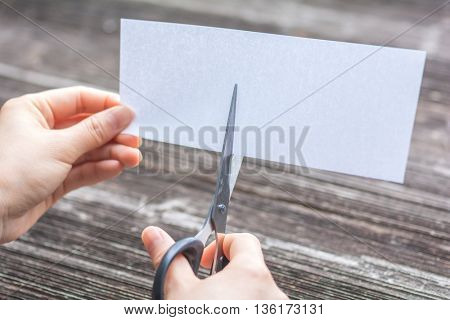 woman cutting paper by scissors