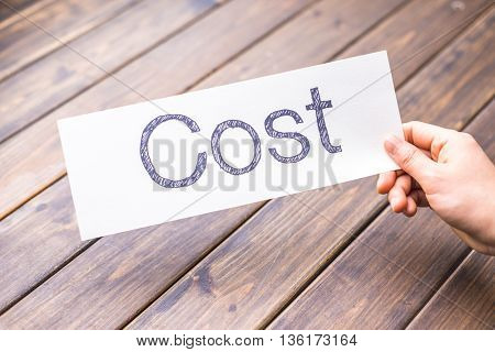 hand hold white paper with word cost