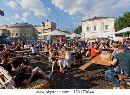 KYIV, UKRAINE - JUN 4, 2016: Young women and men having dinner at outdoor fast-food court under clouds during crowded city festival on June 4, 2016. Kiev is the 8th most populous city in Europe.