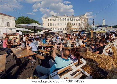 KYIV, UKRAINE - JUN 4, 2016: Crowd of people having lunch at sunny outdoor foodcourt under blue sky during big city weekend fair on June 4, 2016. Kiev is the 8th most populous city in Europe.