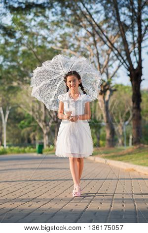Lovely preteen girl with white lace umbrella walking in park