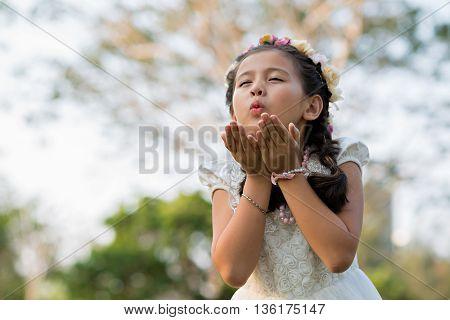 Portrait of pretty little girl in floral wreath sending kiss
