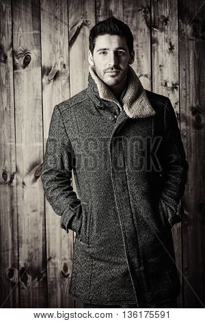 Fashion shot of a handsome male model in jeans and a coat standing by a wooden wall. Men's beauty, seasonal fashion.