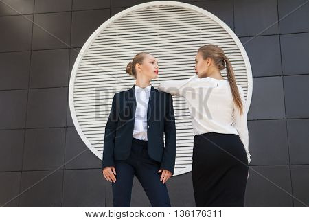Blonde businesswomen in official clothes looking at each other against of building facade