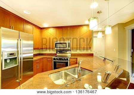 Bright Kitchen Room Interior With Breakfast Bar And Stainless Steel Appliances.