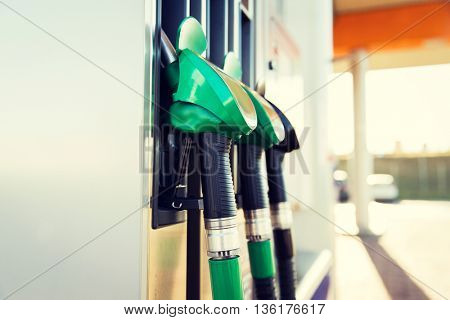 object, fuel, oil, tank and transport concept - close up of gasoline hose at gas station