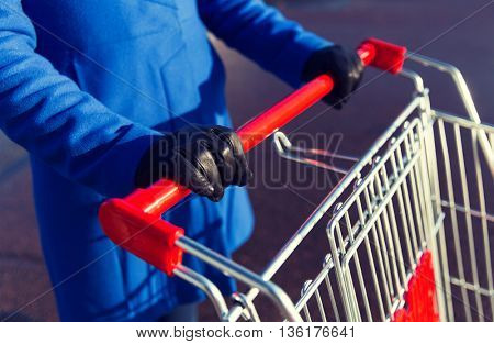 sale, consumerism and people concept - close up of woman with shopping cart on street