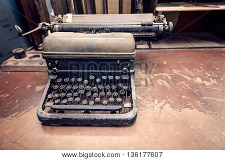Vintage typewriter placed on the desk. Color-toning applied