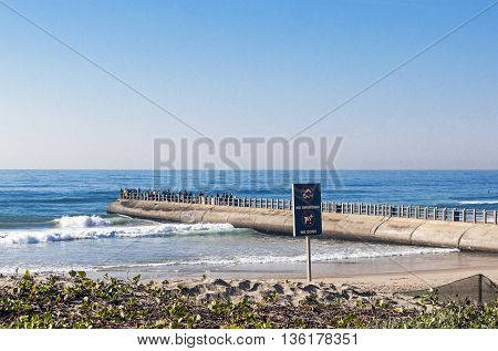 Beach Ocean And Concrete Mier With Many Fisherman