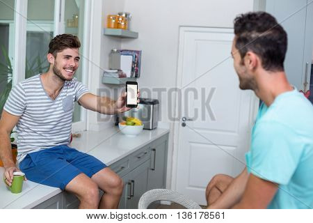 Cheerful man showing phone to friend while sitting in kitchen