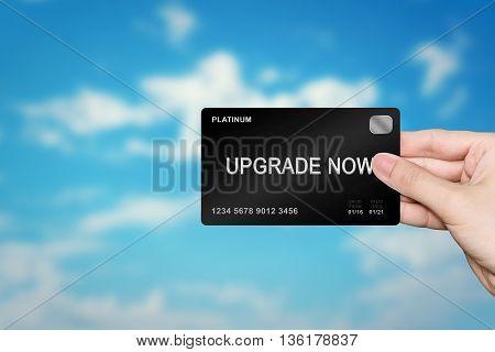 hand picking upgrade now platinum card on blur background