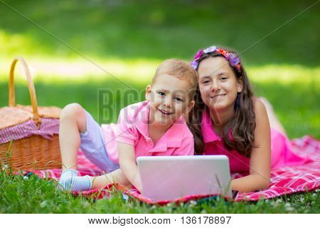 Sister and brother lying down on blanket and using laptop in park