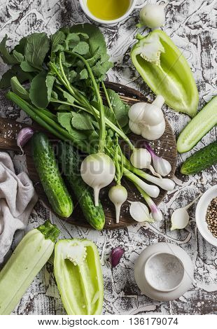 Fresh green and white vegetables - cucumbers peppers radish radish garlic onion and olive oil spices and salt on a light background. Healthy vegetarian food