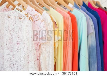 Many different clothes hanging on the rack