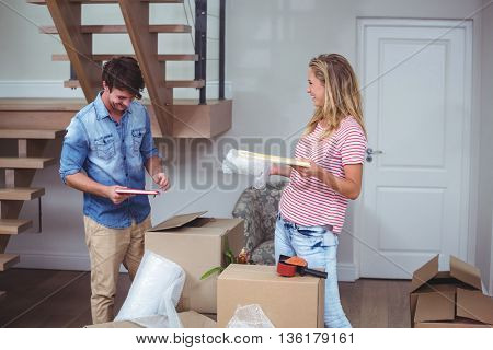 Smiling man and woman unpacking books at home