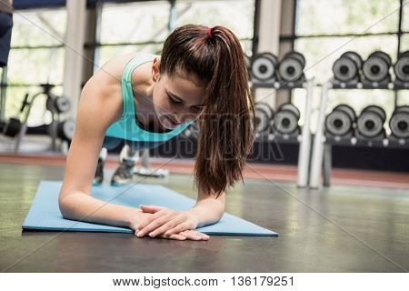 Beautiful woman doing pushups in gym