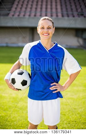 Portrait of female football player holding a ball on football field