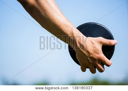 Close-up of hand holding a discus in stadium