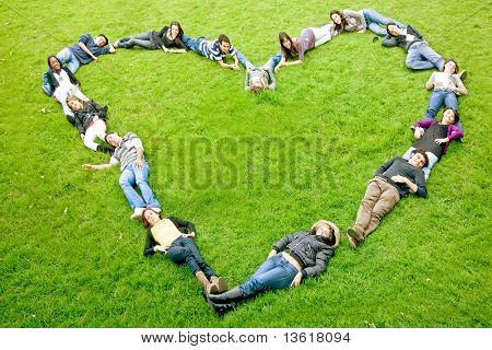 happy group of friends making a heart shape - smiling outdoors in a park