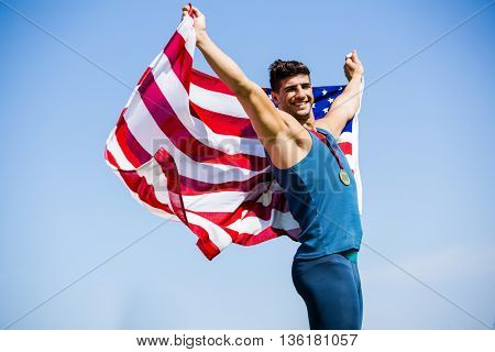 Athlete posing with american flag and gold medals around his neck in stadium